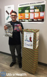 James Gambling, the dispensary manager at Ultra Health's Albuquerque North East location, displays socks in front of donation box in preparation for the Ultra Health Sock Drive.